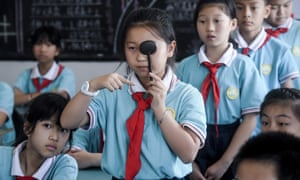 Students line up to get their eyes tested at a primary school in Huzhou City, Zhejiang province.