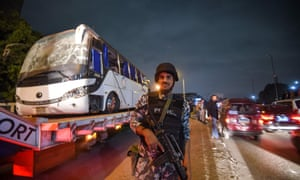 A soldier stands guard as the bus is towed away