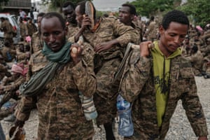 Captive Ethiopian soldiers carry a soldier on a makeshift stretcher.