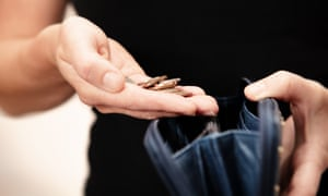 Woman holding money over purseWoman with coins in hand with black leather purse