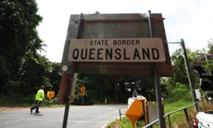 A person stands at a checkpoint on the border of NSW and Queensland