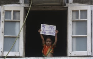 """In Mumbai, a young girl dressed in traditional attire to celebrate Gudi Padwa, or the Marathi New Year, holds a placard with an acronym for the coronavirus that reads """"Nobody should come out on the roads"""""""