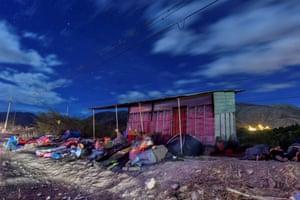 Venezuelans sleep by the side of a motorway in Ecuador