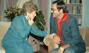 Dr Ruth Westheimer and Burt Reynolds chatting and laughing, Ruth leaning towards BR, touching his wrist with one hand and her cheek with the other