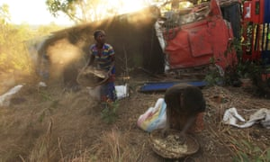 Women and children separate grain from soil in Malawi