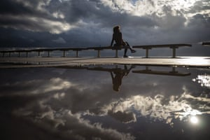 Barcelona, Spain. A woman sits on the sea front after a storm