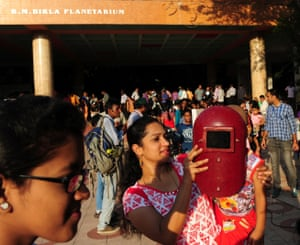 A woman shields her daughters eyes with a welder's mask at The Birla Planetarium