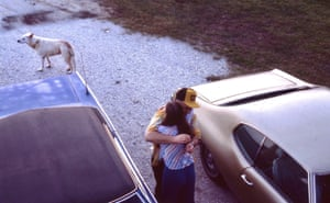 A couple embrace by their cars.