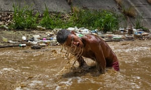 Ronaldo, 19, searches for valuable objects in the Guaire River in Caracas, Venezuela. Because of the national crisis, hundreds of youngsters gather every day in the river, used to dump sewage water and industrial waste, to look for valuable objects they can later sell