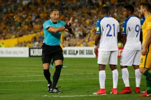 The referee demands that the players in the wall behave.