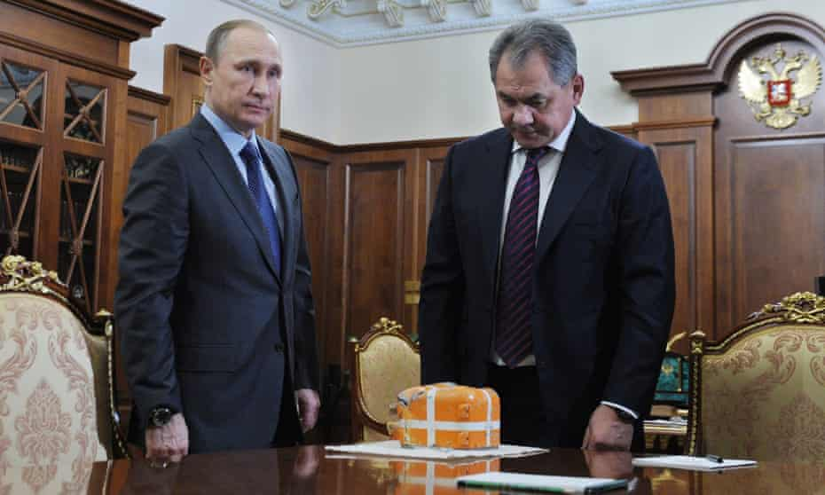 Vladimir Putin and Sergei Shoigu with what is said to be the flight recorder from the Russian SU-24 bomber shot down by Turkey.