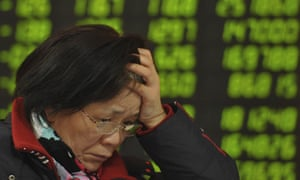 A woman checks stock prices at a brokerage house in Fuyang, in central China's Anhui province