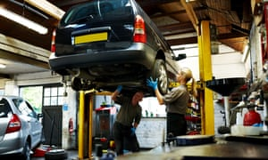 Male and female mechanics working on a car in garage: Female mechanic removing tyre from a car on hydraulic ram while a senior man examining the parts in automobile garageUp and under: apprenticeships offer trainees hands-on experience.
