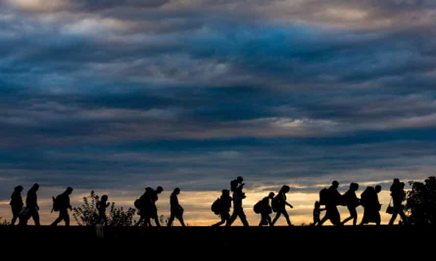 Refugees follow a rail line after crossing the border into Hungary from Serbia