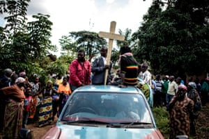 Relatives carry the cross that will be used to mark the grave