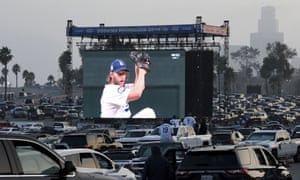 Fans watch Clayton Kershaw pitch from the parking lot of Dodgers Stadium. The World Series is being played in Texas due to Covid-19 restrictions