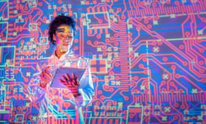 A science student in front of an electronic circuit projection.