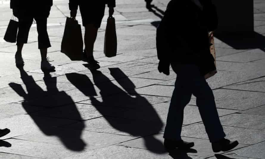 Silhouettes of people walking with bags
