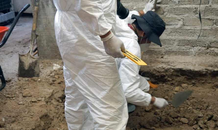 A handout photo released by the Mexico state public prosecutor's office shows forensic personnel during an investigation at the house of alleged serial killer 'Andres' on 20 May.