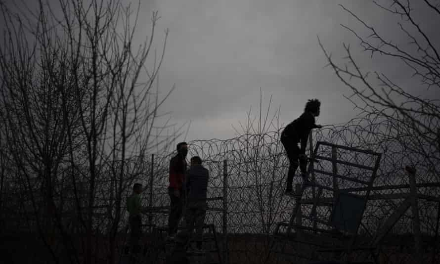 Migrants and refugees attempt to scale the border fence from Turkey into Greece.