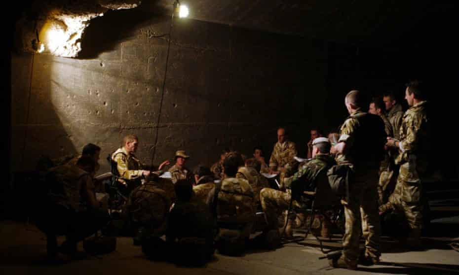 Members of the British Royal Scots Dragoon Guards gather to prepare their battle plans near Basra in Iraq