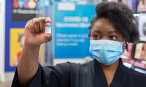 Siphiwe Chungu, pharmacist manager at a chemist in Leeds with a vial of Pfizer which will be administered as the first high street Covid booster vaccination in the UK.