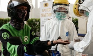 Medical staff conduct a coronavirus rapid test at a drive-through system in Jakarta, Indonesia.