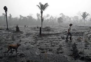Farmer Aurelio Andrade walks through a burnt area of the Amazon rainforest