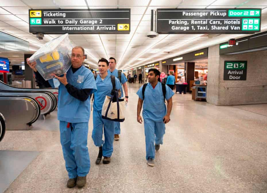 Health officials walk with supplies from a screening area for international arrivals in the terminal at Dulles international airport in Dulles, Virginia.