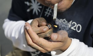 A man lights up a marijuana cigarette.