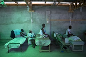 The daughter of 84-year-old Armant Germain replaces the sheets on her bed, in the cholera ward at a hospital in Les Cayes