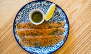 Three strips of pink gravadlax on a blue and white plate with a wedge of lemon