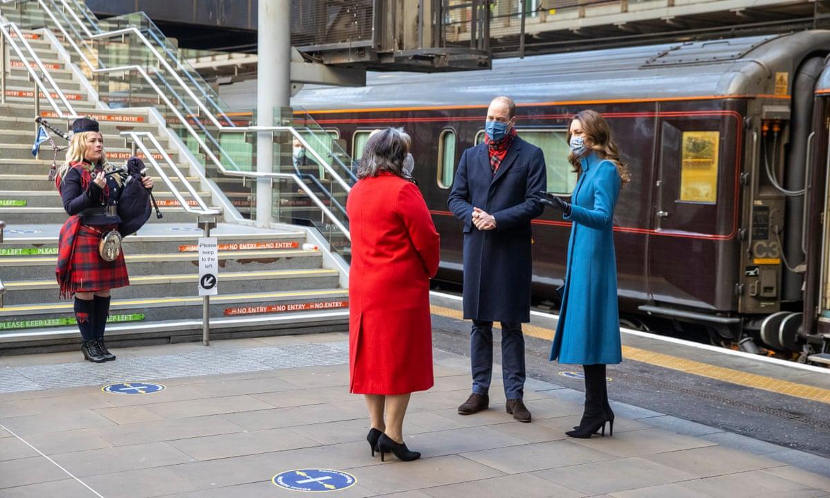 William e Kate conversam com Sanda, que está vestindo um casaco vermelho. A flautista Louise está ao fundo da foto em frente as escadas da estação ela usa roupa xadrez escocesa. William veste um casaco azul escuro, calça jeans, sapatos marrons e um cachecol xadrez. Kate veste um casaco azul celeste, luvas pretas e uma bota de cano longo preta. Ambos usam máscaras.