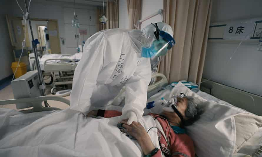 Healthworker in full PPE holds hand of elderly woman in bed wearing oxygen mask