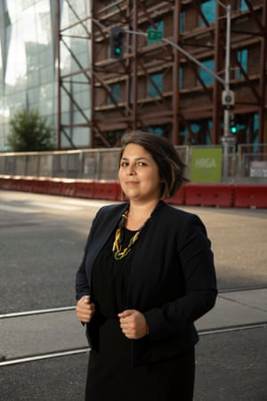 Katie Valenzuela, a longtime Sacramento resident, poses for a portrait in downtown Sacramento in front of the former Hotel Marshall and the Golden 1 Center. Hotel Marshal once housed low-income residents and is now being developed into a Hyatt hotel.