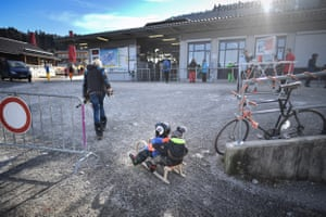 Bavaria, Germany A man drags a sled with two children across a gravel parking lot at a ski resort in Garmisch-Partenkirchen