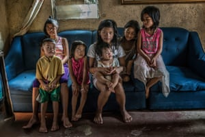 Constantino de Juan's seven children sit on the sofa that bears the bullet hole from their father's shooting