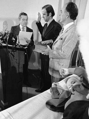 Beau Biden, 4, plays in the foreground as his father Joe Biden is sworn in as US senator by Senate secretary Frank Valeo, left, in a ceremony at a Wilmington hospital on 5 January 1973. Beau was injured in a December accident that killed his mother and sister. Biden's father-in-law, Robert Hunter, holds the Bible.