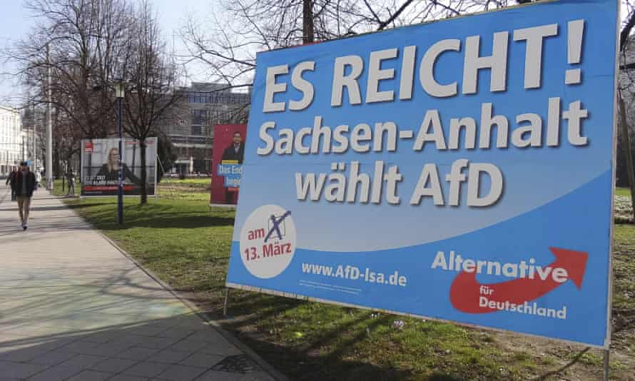"""A man walks past a campaign poster of right-populist AfD party reading """"It's enough - Saxony-Anhalt elects AfD"""" in Magdeburg, Germany."""