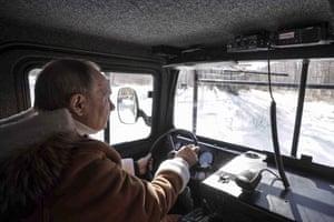 Putin is seen behind the wheel.