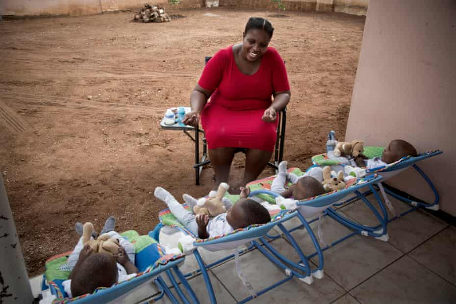 Keneilwe Ditsile feeds and plays with her quadruplet sons outside her family's home in Gaborone, Botswana.