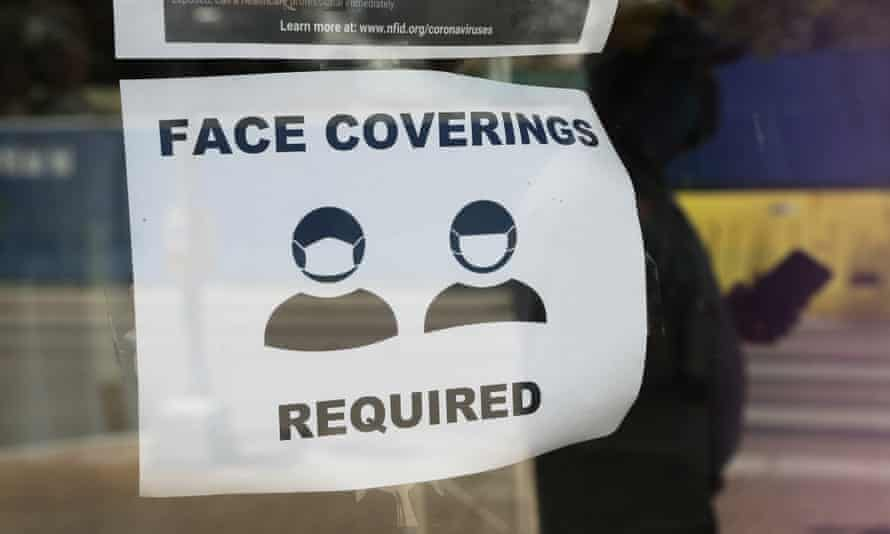 A visitor wearing a mask to protect against the spread of Covid-19 passes a sign requiring masks in San Antonio.