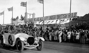 """The Prince of Wales in Aden November 12, 1921, to visit troops passes locals and a banner asking him to """"Tell Daddy we are all happy under British rule"""". Daddy was King George V."""