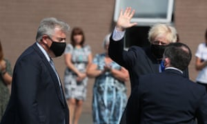 Boris Johnson (C) waves flanked by Northern Ireland Secretary Brandon Lewis (L) and Northern Ireland's Health Minister Robin Swann (R), all wearing facemasks as a precaution against the spread of the novel coronavirus as they arrive to visit the Northern Ireland Ambulance Service HQ in Belfast on 13 August (Photo by Brian Lawless/AFP via Getty Images)