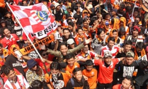 Dressed in their trademark orange uniforms, Jakmania fans protest following violent clashes with the police.