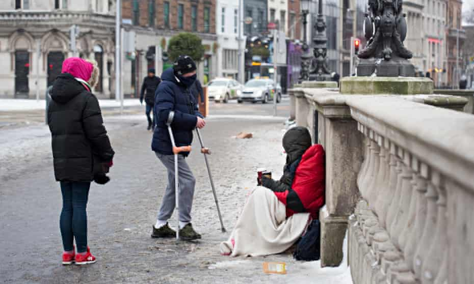 Passersby talk to a homeless person in Dublin