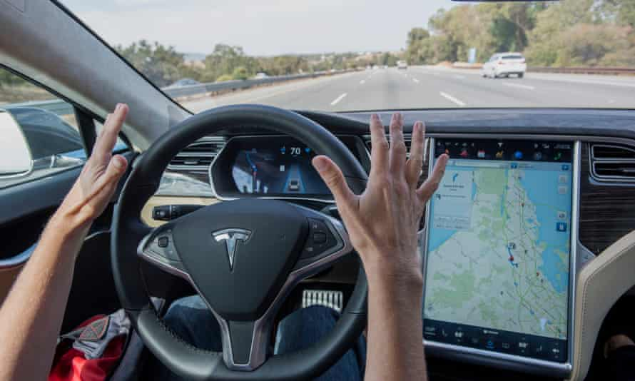 A driver with hands off the wheel in a Tesla.
