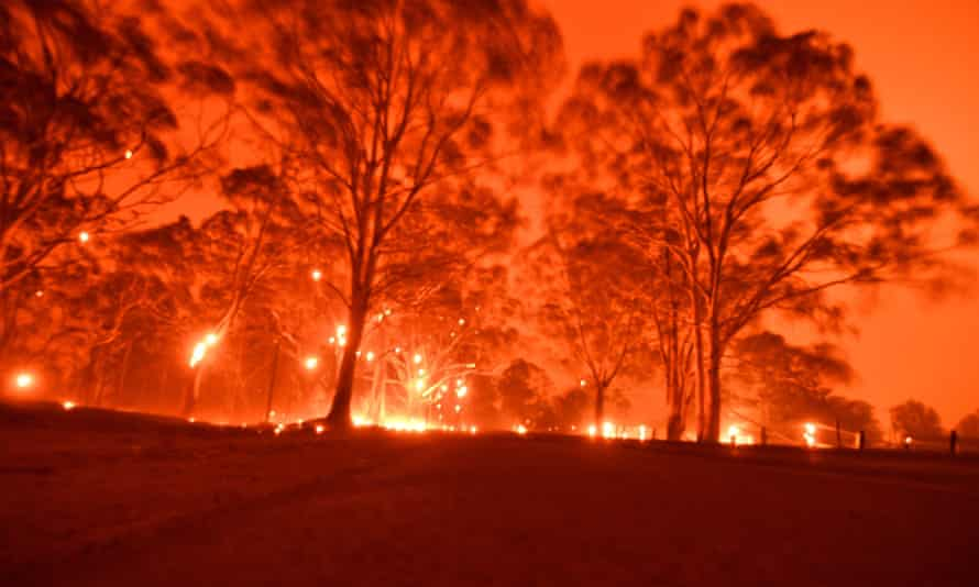 Glowing orange sky over burning forest in NSW
