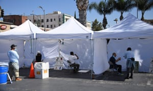 People use a mouth swab to collect their own sample at a walk-up coronavirus testing location in Los Angeles, California, on 10 August.