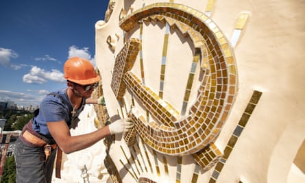A worker cleans a sculpture of the hammer and sickle symbol at the VDNKh in Moscow.